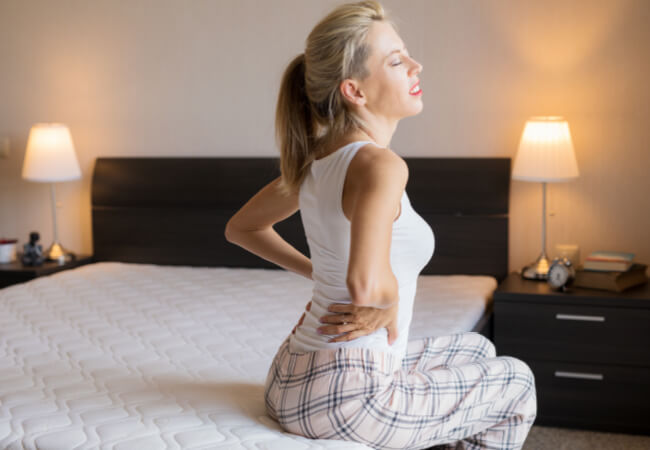 woman with back pain on a bed